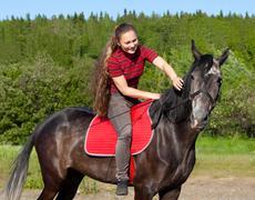 A girl with her hair stroking horse Stock Photos