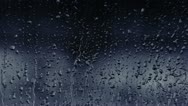 Blue rain drops on window glass Stock Footage