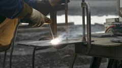 Close tight shot of welder joining plates of steel Stock Footage