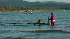 Filipino woman catching Milkfish fry in shallow water in Philippines Stock Footage