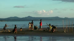 Children playing on Datu Sumakwel Beach during a vivid sunset in Philippines Stock Footage