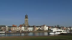 Cargo ship on river IJssel passing Hanseatic town of Deventer, The Netherlands - stock footage