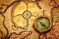Vintage compass lies on an ancient map of the north pole. Stock Photos