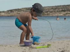 Cute kid playing on the beach, super slow motion, shot at 240fps NTSC Stock Footage