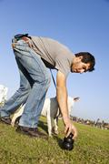 Trainer placing dog chew toy for bull-terier at park Stock Photos