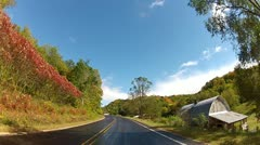 Driving on midwestern country road in fall with farms, fields, trees Stock Footage