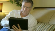 Mature man smiles while using a tablet pc Stock Footage