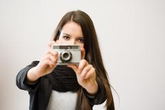 Stock Photo of brunette girl with retro film camera.