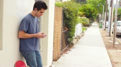 Young Man Teen Male Grunge Texting Outside Listening to Music Stock Footage