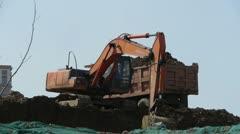 Excavator working & dumper truck on construction site. - stock footage