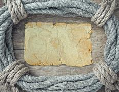 frame made of twisted rope and blank old paper form for records - stock photo