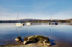 lake windermere with three boats and a rock - stock photo