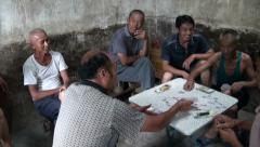 Chinese villagers play cards in a small town Stock Footage