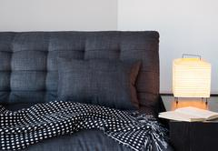 Cozy gray sofa, table lamp and book - stock photo