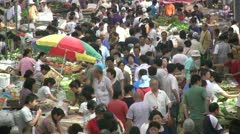 People visit shop at a busy crowded fruit vegetable market in China Stock Footage