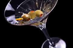 martini on black with olives tilted - stock photo