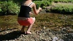 Woman shorts sit stream throw pebble stones flow water walk away Stock Footage