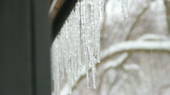 Melting icicles and snowy background Stock Footage