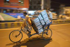 Man transporting merchandise on old tricycle Stock Photos