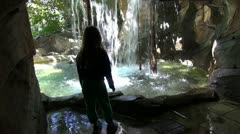 Young girl amazed by waterfall - stock footage