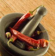 Stone mortar with red chillies Stock Photos