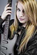 sexy young blonde dressed in black leather holding electric guitar - stock photo