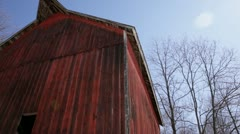 Abandoned 1910 rural homestead - red barn, low angle pan right to left Stock Footage