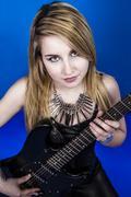 Beautiful young blonde playing electric guitar Stock Photos