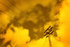 Telegraph pole over sunset sky background Stock Photos