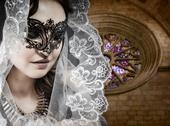 Virgin, woman in veil and black dress with venetian mask in gothic cathedral Stock Photos