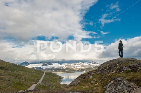 Stock photo of silhouette of traveler at scenic 55 road, norway