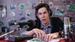 Lazy sport event commentator (radio dj) eats mini football because boring game - stock footage