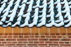 Icicles on the roof of an old dutch farm Stock Photos