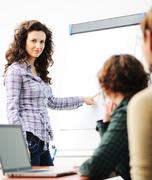 female executive making  presentation to her colleagues in modern enviroment - stock photo
