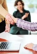 Closing a successful deal with a handshake. signed contract and applause in t Stock Photos