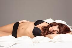 smiling woman in lingerie in the bed - stock photo