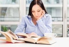 Female student learning at home with different books Stock Photos