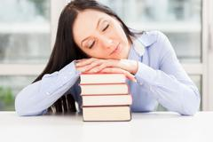 pretty student sleeping on book pile - stock photo