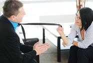 Stock Photo of woman pulling male partner's tie in discussion