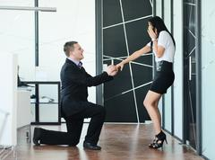 Young man romantically proposing to girlfriend and offering engagement ring a Stock Photos