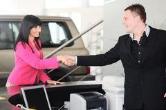 Man handing woman automobile keys for the new car Stock Photos