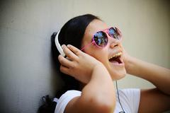 beautiful teenage girl listening to music on headphones and enjoying - stock photo