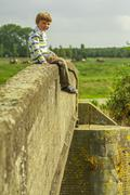 Kid sitting on bridge Stock Photos