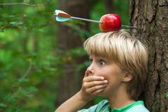 kid with apple on his head and arrow shot through - stock photo
