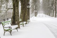 snow covered benches in a park - stock photo