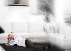 Elderly man having heart attack lying on floor at home Stock Photos