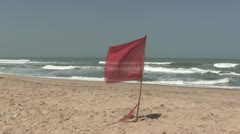 Red warning flag flying on a deserted beach. Stock Footage