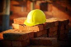 Under construction, helmet and bricks for building site Stock Photos
