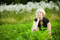 Stock Photo of pensive girl in a field of flowers