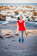 girl walking along the beach - stock photo